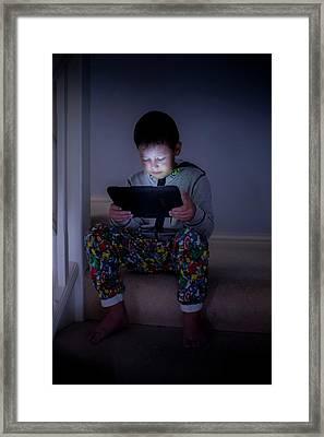 Boy Using A Digital Tablet In The Dark Framed Print by Samuel Ashfield