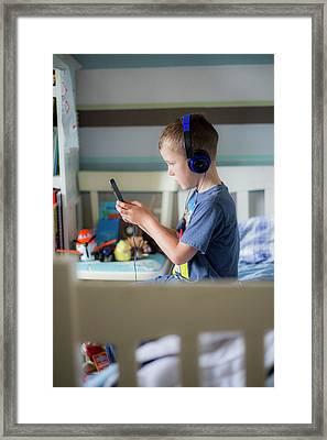 Boy Wearing Headphones Using Device Framed Print by Samuel Ashfield