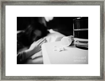 Glass Of Water And Bottles Of Sleeping Pills On Bedside Table Of Early Twenties Woman In Bed In A Be Framed Print by Joe Fox