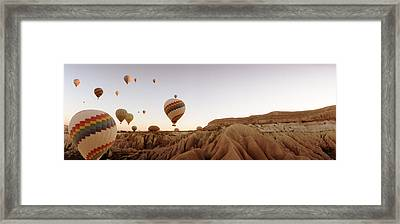 Hot Air Balloons Over Landscape Framed Print by Panoramic Images