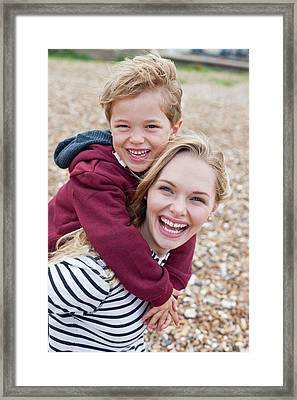 Mother Giving Son Piggy Back Framed Print by Ian Hooton
