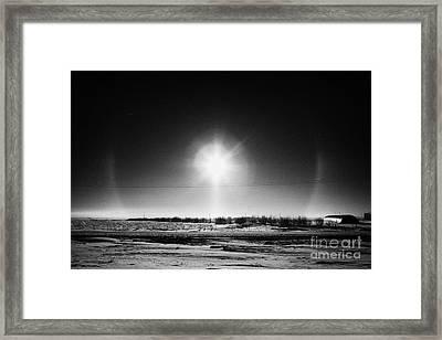 sun dog parhelion halo due to ice crystals surrounding the sun in Saskatchewan Canada Framed Print by Joe Fox