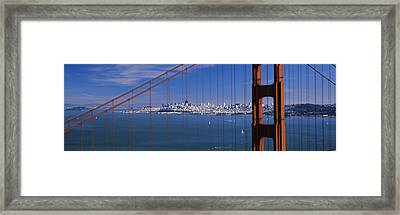 Suspension Bridge With A City Framed Print by Panoramic Images