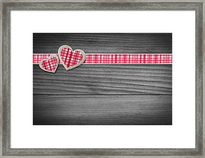 Two Hearts Laying On Wood  Framed Print by Aged Pixel