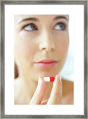 Woman Holding A Red And White Capsule Framed Print by Ian Hooton