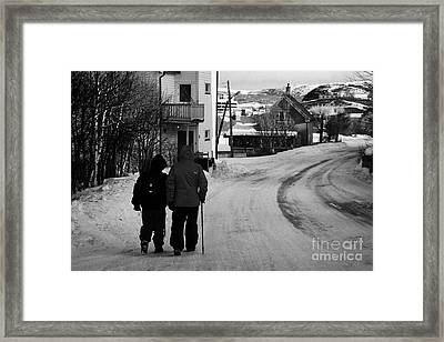 Middle Aged Couple Walking Along Snow Covered Street With Sticks Kirkenes Finnmark Norway Europe Framed Print by Joe Fox