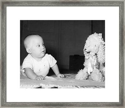 A Baby And A Toy Dog Framed Print by Orville Andrews
