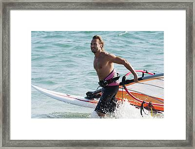 A Man Comes Walks In The Water With His Framed Print by Ben Welsh