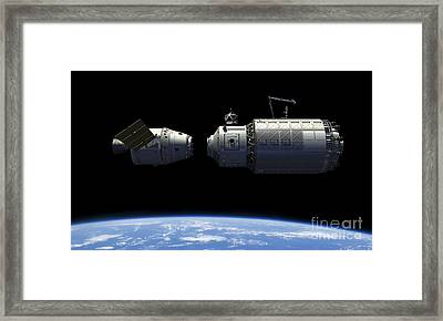 A Manned Reusable Crew Capsule Docks Framed Print by Walter Myers