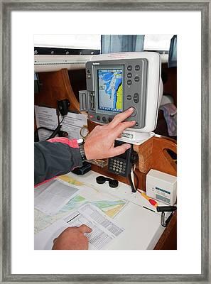 A Sailor Using Gps Navigation Equipment Framed Print by Ashley Cooper