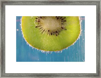 A Slice Of Kiwi Fruit In A Glass Framed Print by Brian Jannsen