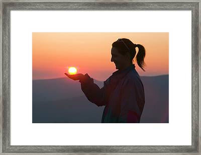 A Woman Holding The Setting Sun Framed Print by Ashley Cooper