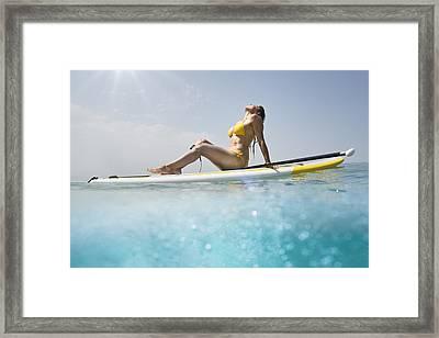 A Woman In A Yellow Bikini Sits Framed Print by Ben Welsh