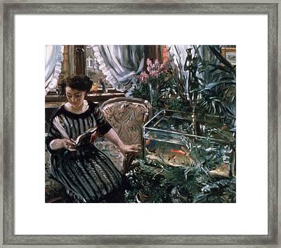 A Woman Reading Near A Goldfish Tank Framed Print by Lovis Corinth
