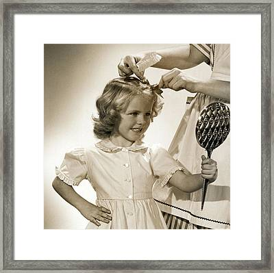 A Young Girl Gets A Bow Framed Print by Underwood Archives