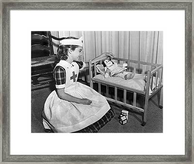 A Young Girl Plays Nurse To Her Little Lulu Doll. Framed Print by Underwood Archives