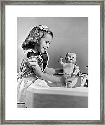 A Young Girl Plays With Her New All-vinyl Plastic Doll That Can Framed Print by Underwood Archives