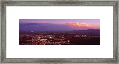 Aerial View Of A City Lit Up At Sunset Framed Print by Panoramic Images