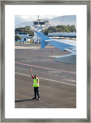 Airport Worker Guides Jet Airliner Framed Print by Jim West