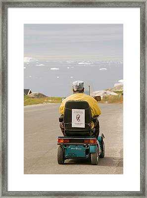 An Inuit Man In A Mobility Scooter Framed Print by Ashley Cooper
