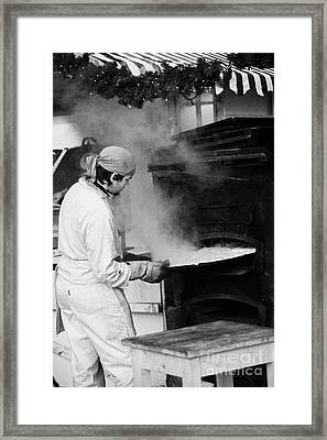 Baker Removing Tray Of Bread From An Outdoor Wooden Baking Oven On A Stall With Steam Escaping At The Christmas Market Berlin Germany Framed Print by Joe Fox
