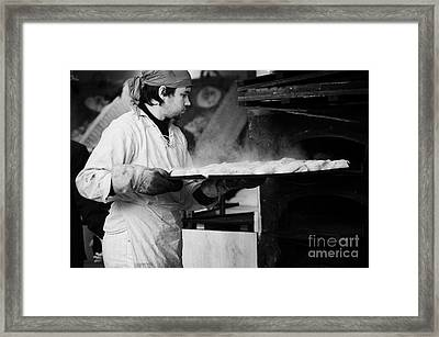 Baker Removing Tray Of Bread With Steam Rising From An Outdoor Wooden Baking Oven On A Stall At The Christmas Market Berlin Germany Framed Print by Joe Fox