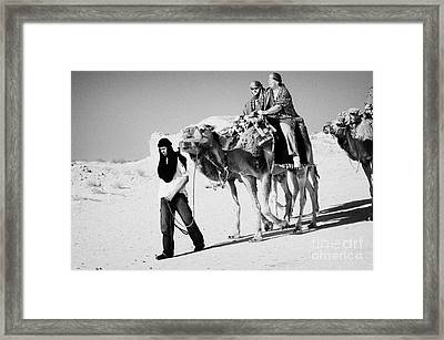bedouin guide in modern clothing leads british tourists riding camels and wearing desert clothes into the sahara desert at Douz Tunisia Framed Print by Joe Fox