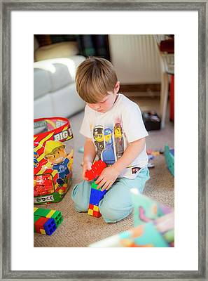 Boy Playing With Plastic Bricks Framed Print by Samuel Ashfield