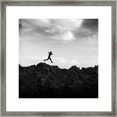 Boy Running Over Dirt Pile Framed Print by Donald  Erickson