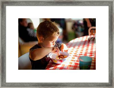 Boy Sitting At Table Eating A Meal Framed Print by Samuel Ashfield