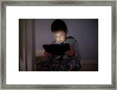 Boy Using A Digital Tablet In The Dark Framed Print by Samuel Ashfield