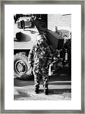 British Army Soldier In Riot Gear With Saxon Armoured Personnel Carrier Vehicle On Crumlin Road At A Framed Print by Joe Fox