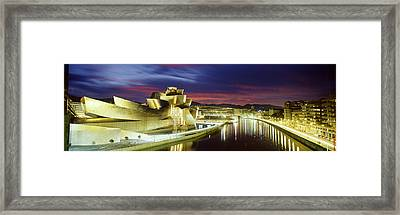 Buildings Lit Up At Dusk, Guggenheim Framed Print by Panoramic Images