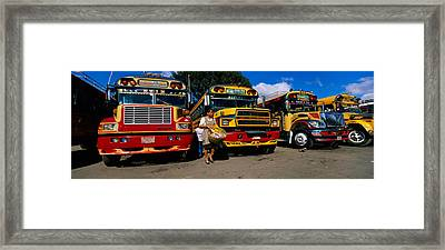 Buses Parked In A Row At A Bus Station Framed Print by Panoramic Images