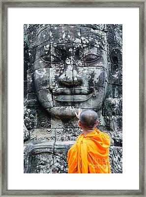 Cambodia - Angkor Wat - Monk Touching Giant Buddha Statue Framed Print by Matteo Colombo
