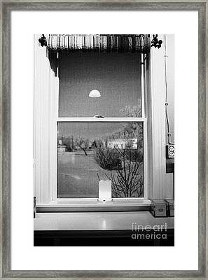 Candle In The Window Looking Out Over Snow Covered Scene In Small Rural Village Framed Print by Joe Fox