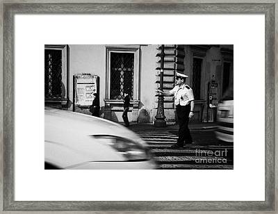 car drives across crossing as Roman Municipal policeman directs traffic at a pedestrian crossing in the Via Teatro Marcello Rome Lazio Italy Framed Print by Joe Fox