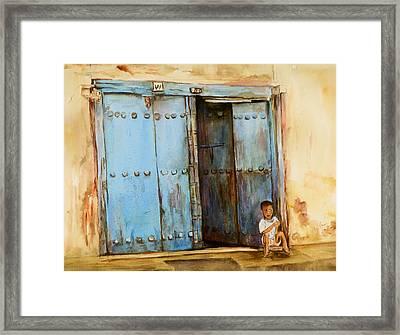 Child Sitting In Old Zanzibar Doorway Framed Print by Sher Nasser
