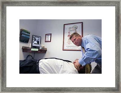 Chiropractor Manipulating Patient Framed Print by Jim West