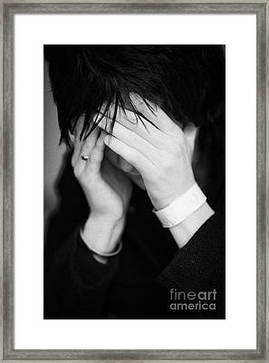 Close Up Of Young Dark Haired Teenage Man Sitting With His Head In His Hands Hiding His Face Staring Framed Print by Joe Fox