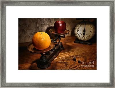 Comparing Apple And Orange Framed Print by Olivier Le Queinec