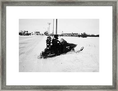 couple on a snowmobile going off road Kamsack Saskatchewan Canada Framed Print by Joe Fox