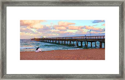 Couple Sitting On The Beach At Sunset Framed Print by Panoramic Images