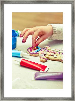 Decorating Gingerbread Man Framed Print by Tom Gowanlock