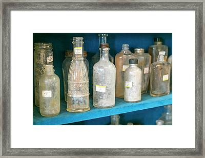 Dirty Antique Glass Bottles On Display Framed Print by Julien Mcroberts