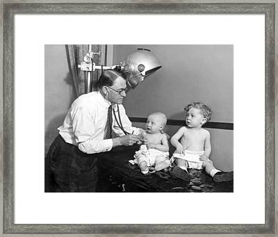 Doctor Examines Baby Framed Print by Underwood Archives