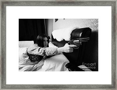 Early Twenties Woman Frightened Pointing Handgun Towards Door In Bed In A Bedroom Framed Print by Joe Fox