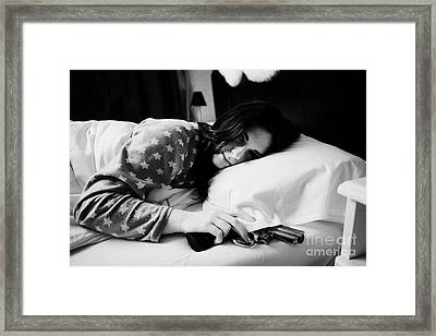 Early Twenties Woman Waking With Hand On Handgun Under Pillow At Night In Bed In A Bedroom Framed Print by Joe Fox