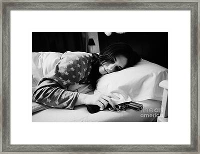 Early Twenties Woman With Hand On Handgun Under Pillow At Night In Bed In A Bedroom Framed Print by Joe Fox