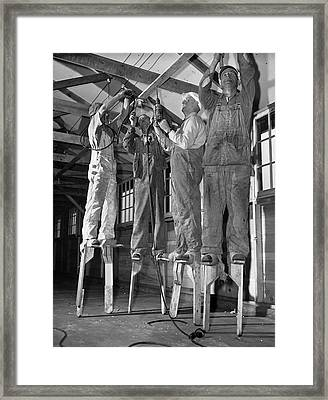 Electricians On Stilts Framed Print by Underwood Archives